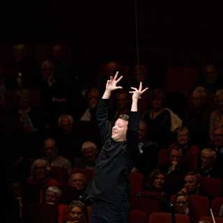 Ryan Bancroft løfter DR SymfoniOrkestret fra podiet i Malko-konkurrencens finale, som han fredag aften fik 1. pladsen i.