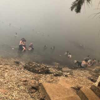 Turister har søgt ned mod stranden for at komme væk fra flammerne. Man kan fornemme, hvor meget røg der er i luften. Lasse Birch tog billedet, da han flygtede fra sit hotel.