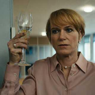 Anna (Maria Rich) løfter glasset for den yngre medarbejder, som hun har oplært over årene, der netop har snuppet en forfremmelse for næsen af hende. Et nederlag for Anna, der er medvirkende til, at hun skubbes over kanten og ind i en kriminel verden.