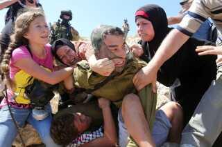 Flere forsøger at få drengen fri af soldatens greb. AFP PHOTO / ABBAS MOMANI