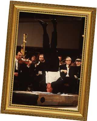 På hovedet. Yeudi Menuhin dirigerer Berliner Philharmonikerne, mens han står i en noget krævende yogaposition ...