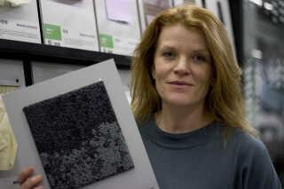 På billedet holder Mette Bak-Andersen, leder af Material Design Lab på Københavns Erhvervsakademi en prøve på det gulvtæppe, som er udviklet på Filippinerne af fiskenet.