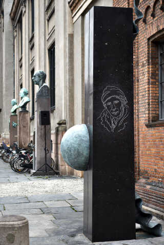 Skulptur til ære for seismolog Inge Lehmann, lavet af billedhugger Elisabeth Toubro. Kuglen symboliserer Jorden, som Lehmann som den første beviste har en fast kerne. Skulpturen står på Frue Plads side om side med store danske (mandlige) videnskabsmænd. Skulpturen repræsenterer et skridt i den rigtige retning for flere kvinder i det offentlige rum.