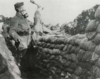 To soldater fra 9. jægerbataljon med gasmasker og håndgranater i skyttegrav ved Givenchy i Frankrig. Bagerst soldat ved navn Ravnsgaard fra Christiansfeld.