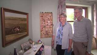 Ellen og Ejnar Bæk ser på et billede af sønnen Uffes gård. På væggen ved siden af hænger datteren Birgittes sættekasse. Foto: Morten Sørensen, Gistrup Film