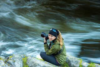 Helle sidder ved en flod ved parrets campområde i Oulanka National Park, Finland.