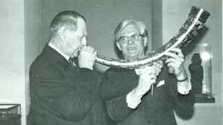 Den hornblæsende konge Frederik den Niende. Rigsantikvar og daværende direktør for Nationalmuseet holder hornet.