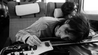 Glad for sin guitar. Patti Smith på toget fra Manchester til London i 1978.