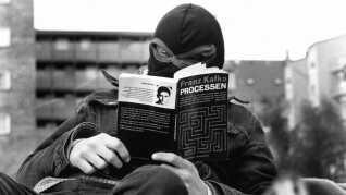 En maskeret BZ'er læser Franz Kafka