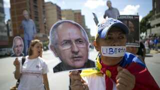 Tilhængere af Antonio Ledezma bærer skilte med billeder af den fængslede borgmester under en demonstration i hovedstaden Caracas.