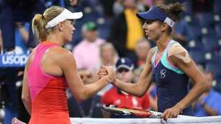 Caroline Wozniacki takker Mihaela Buzarnescu for kampen på Grandstand på Flushing Meadows-anlægget i New York.