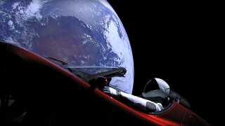 Elon Musks Tesla Roadster i kredsløb med en dukke om bord. I baggrunden ses Jorden.