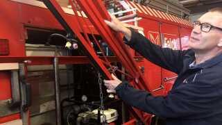 Preben Trolle viser, hvordan den gamle landbrugssprøjte er blevet monteret på bagenden af den lille brandbil.