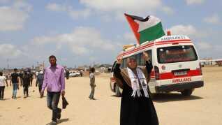En palæstinensisk kvinde vifter med et flag under fredagens demonstration.