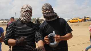 To maskerede palæstinensere styrer en drage mod Israel. Drager, israelere kalder 'terror-drager', fordi de ødelægger marker og afgrøder.