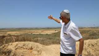 Israelske Eyal Majbi peger mod grænsen til Gaza få hundrede meter væk. I hans område er marker brændt af af palæstinensiske drager og balloner.