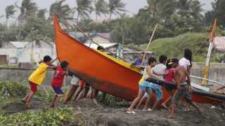 Fiskere sikrer en båd ved at trække den på land.