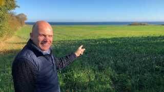 Niels Feerup står og peger ud på den mark, hvor man i 2020 forventer at tage det første spadestik til Nordals Ferieresort.
