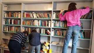 Ida Schneider (tv.), Alba Larsen og Karoline Hjemkær (th.) rydder ud og gør rent på Ryslinge Efterskoles bibliotek på Dagsværkdagen.
