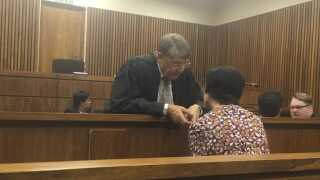 Forsvarsadvokat Piet du Plessis taler med sin klient.