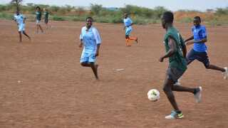 Det var en mark som denne, at Mabil (i grønt) spillede fodbold som barn.