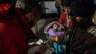 En migrantkvinde holder sit nyfødte barn, efter at være blevet reddet på Middelhavet af Proactiva Open Arms.
