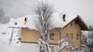 Myndighederne pålægger husejere at fjerne sne fra tagene, da den tunge sne risikerer at få tagene til at kolapse. Her bliver der ryddet sne i landsbyen Filzmoos.