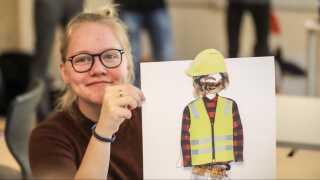 """Sådan ser en """"kønsneutral"""" håndværker ud, hvis man spørger 9. klasse på Susåskolens afdeling i Glumsø. Alberte Jensen viser resultatet af gruppearbejdet, hvor eleverne skulle klæde en dukke på som håndværker. - Det har sat en masse tanker i gang hos mig, om at kvinder også kan lave håndværksmæssige ting, siger Alberte Jensen."""