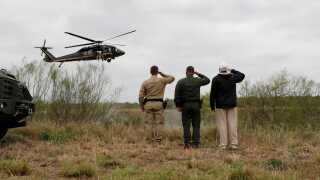 Præsident Donald Trump gør honnør, da en U.S. Border Patrol-helikopter flyver over Rio Grande-floden.