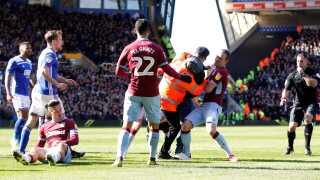 Sikkerhedsvagter og Aston Villa-spillere forsøger at få styr på den aggressive fan.