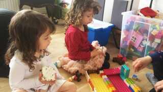 Søstrene Scarlett på tre år og Malajka på fire sidder og leger ved legehjørnet i hjemmet, hvor Wilhelmina Magallanes har sin private pasningsordning.