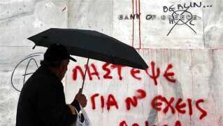 En mand passerer Bank of Greece, der i ly af nattens uro i Athen er blevet omdøbt til bank of Berlin, med henvisning til den europæiske og især tyske indblanding i grækernes økonomi. Men når uroen har lagt sig, er der nok at tage fat på for grækerne, skriver Ole Ryborg.