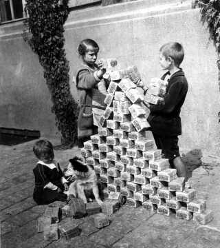 Hyperinflation! Børn leger med værdiløse bundter af tyske mark i 1923. Lige efter Versaillestraktaten i 1919 faldt værdien af en mark, så der skulle 48 til for at købe en amerikansk dollar. Men inflation betød, at det i 1922 kostede omkring 320 mark per dollar. Det blev derfor umuligt for Tyskland at betale krigsskadeerstatningen, og seddelpressen roterede for at trykke flere penge. I november 1923 svarede én dollar til 4,210,500,000,000 mark!