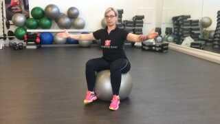 Øvelse 4: Træning af mave med bold. Sug maven ind, og find balancepunktet ved at løfte fødderne fra gulvet. Hold spændingen i maven og læg vægten fra side til side samt frem og tilbage.
