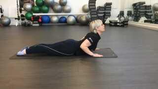 Øvelse 2: Udstrækning af lænd. Man ligger sig på maven, spænder ballerne og placerer hænderne i gulvet tæt på kroppen. Svajer i ryggen og løft overkroppen så langt op, man kan. Læg hovedet tilbage og hold strækket så længe man kan. Gentag øvelsen nogle gange.