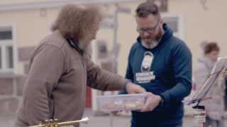 Claus Ruhe Madsen deler pølsehorn ud.