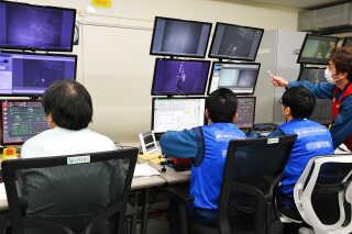 Medarbejdere styrer de kraner, der løfter brændstofbeholderne ud af nedkølingsrummet fra et kontrolrum 500 meter væk.