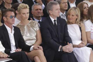 Direktør for LVMH-gruppen Bernard Arnault og hans kone Helene til modeshow i Paris. Til venstre for parret sidder skuespillerne Sean Penn og Charlize Theron.