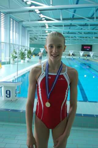 Julie i svømmehallen med en af sine mange medaljer.
