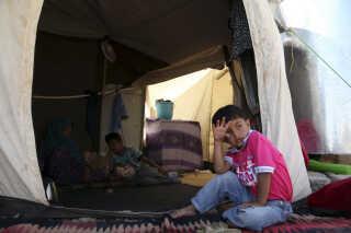 En syrisk flygtningedreng fordriver tiden i Arbart-flygtningelejren i det nordlige Irak.