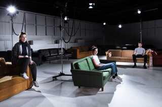 Under forestillingen er publikum bænket i bløde sofaer, mens skuespillerne bevæger sig frit omkring i rummet.