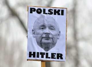 Spændingerne stiger i Polen. En demonstrant sammenligner her PiS' partileder, Jaroslaw Kaczynski, med Hitler.