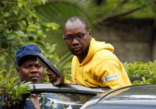 Politiet fører Evan Mawarire ind i en bil i hovedstaden Harare.