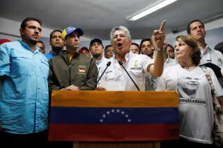 Henry Ramos Allup , en af oppositionsalliancen MUDs politiske ledere, taler på et pressemøde. Med kasketten ses Henrique Capriles, der to gange har været oppositionens præsidentkandidat.  Ramos Allup blev valgt til formand for Nationalforsamlingen, da MUD vandt flertallet i 2015.