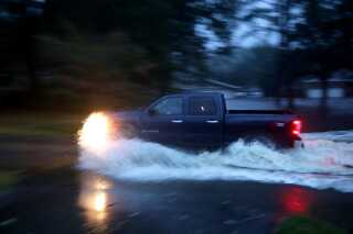 En billist kører gennem oversvømmelser fra Neuse-floden i River Bend, North Carolina.