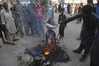 Pakistanske demonstranter brænder et billede af Aasia Bibi i byen Hyderabad i Pakistan. Radikale islamister har krævet, at hun bliver offentligt henrettet (AP Foto/Pervez Masih )