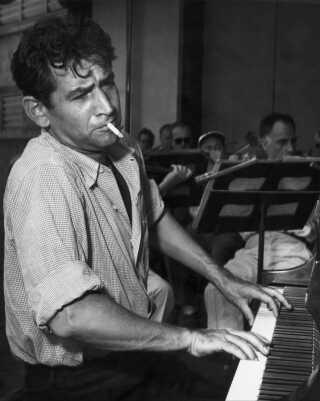 Den unge Bernstein ved klaveret med smøgen i kæften - og orkestret i baggrunden.