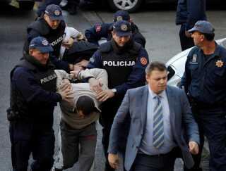 Politiet i Montenegro eskorterer en formodet kupmager til retten.