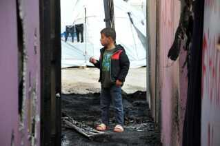 Et barn står mellem teltene i Souda-lejren på den græske ø Chios, hvor en syrisk flygtning forleden blev hårdt såret, og flere andre fik deres telte brændt ned, da nogle personer kastede sten og brandbomber mod lejren.