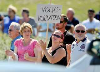 """Angela Merkel bliver kaldt """"Folkeforræder"""" som der står på skiltet her. AFP PHOTO / DPA / JAN WOITAS"""